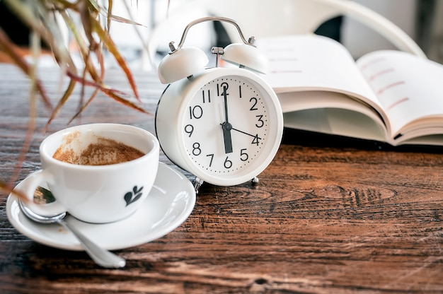 Réveil blanc et tasse de café sur une table en bois avec espace de copie.