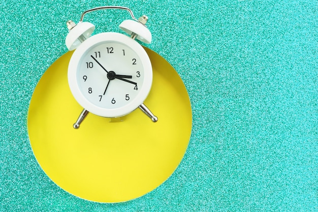 Réveil blanc tombant dans un trou rond dans un carton turquoise brillant sur un fond jaune. espace pour le texte.