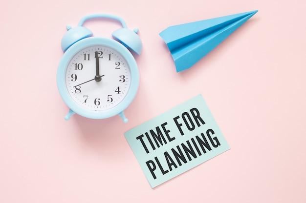 Réveil bleu, avion en papier bleu et time for planning blue post it sur fond rose clair