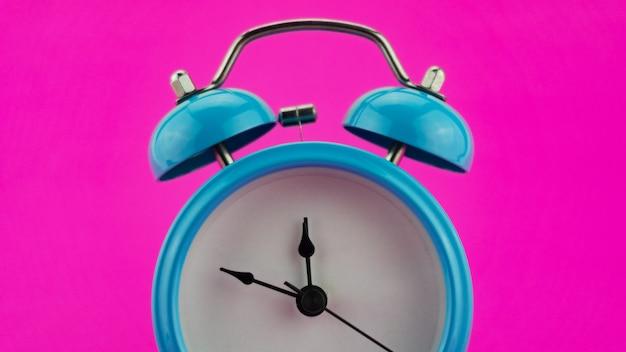 Réveil bleu sur fond rose avant douze heures le soir du réveillon du visage de beau réveil indiquant minuit adorable célébration du nouvel an, concept bonne année 2022.