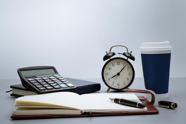Réveil avec bloc-notes, calculatrice, stylo et tasse de café sur fond gris