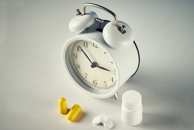 Réveil, bouchons d'oreille et pilules sur blanc