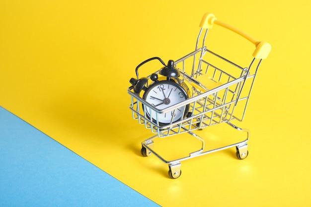 Réveil en caddie miniature sur fond jaune copie espace