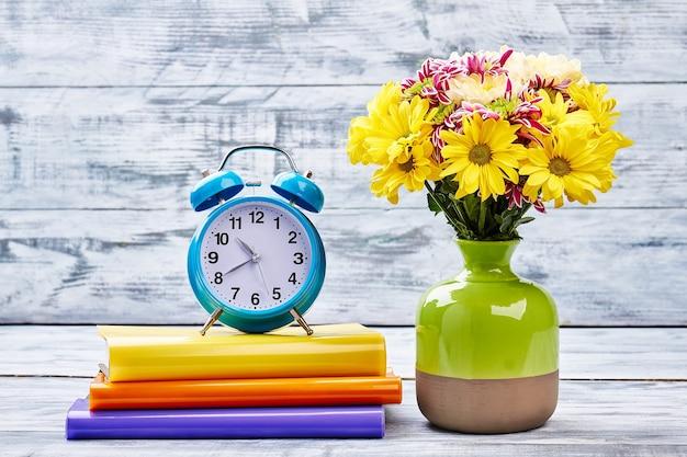 Réveil, cahiers et fleurs. ambiance créative.