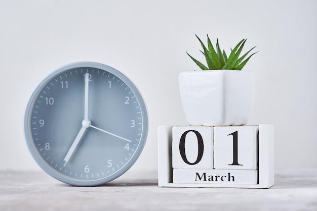 Réveil avec calendrier en bois bloc date 1er mars et plante sur table