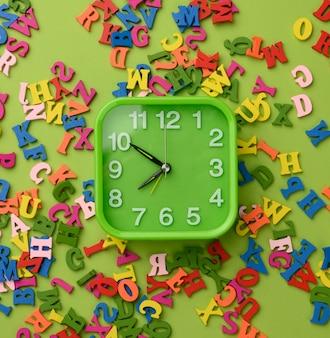 Réveil carré et lettres en bois multicolores de l'alphabet anglais sur une surface verte, vue du dessus