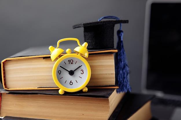 Réveil, chapeau de graduation et livres sur table.