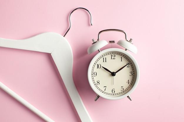 Réveil et cintre sur une surface rose