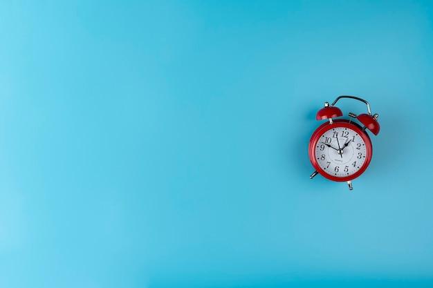 Réveil de couleur rouge sur fond bleu avec un espace de copie concept d'horloge isolée de l'image du temps