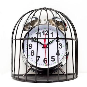 Réveil enfermé dans une cage.