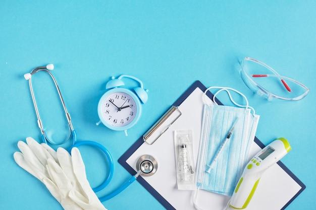 Réveil et équipement médical sur un fond bleu place copie vue de dessus stéthoscope thermomètre sans contact masque facial seringue lunettes de sécurité et gants