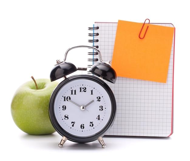 Réveil, feuille de cahier vierge et pomme. accessoires d'études pour écoliers et étudiants. retour au concept de l'école.