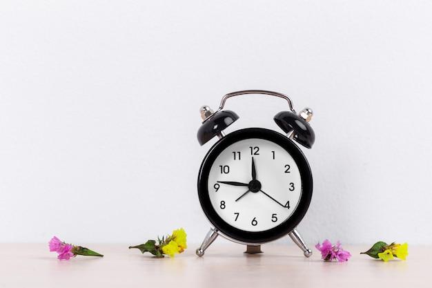 Réveil avec des fleurs séchées sur une table se bouchent