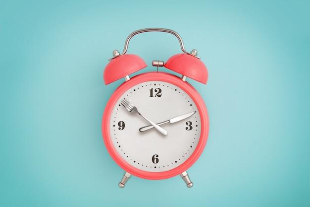 Réveil. fourchette et couteau au lieu d'aiguilles d'horloge. concept de jeûne intermittent, de déjeuner, de régime et de perte de poids
