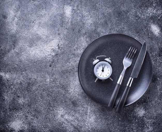 Réveil gris dans une assiette vide.