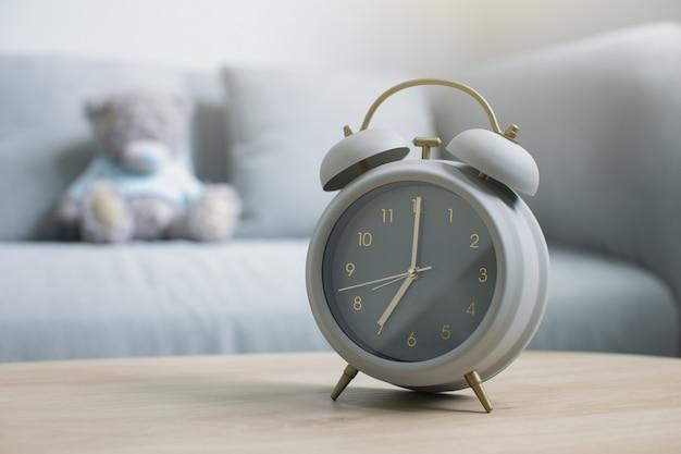 Réveil gris sur une table en bois dans la lumière du matin dans le salon