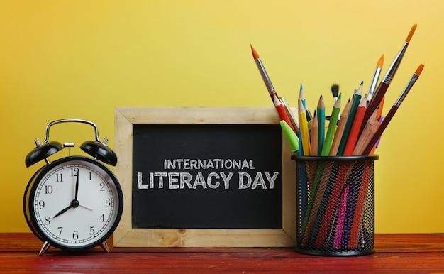 Réveil international d'alphabétisation, tableau noir et papeterie scolaire en panier jaune