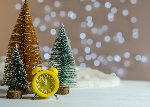 Réveil jaune et un arbre de noël sur la table