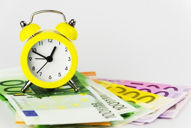 Réveil jaune et billets en euros de différentes coupures