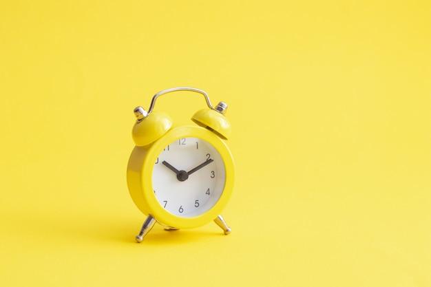 Réveil jaune classique sur fond jaune.