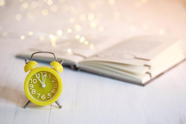 Réveil jaune et livre sur un tableau blanc. décorations de noël