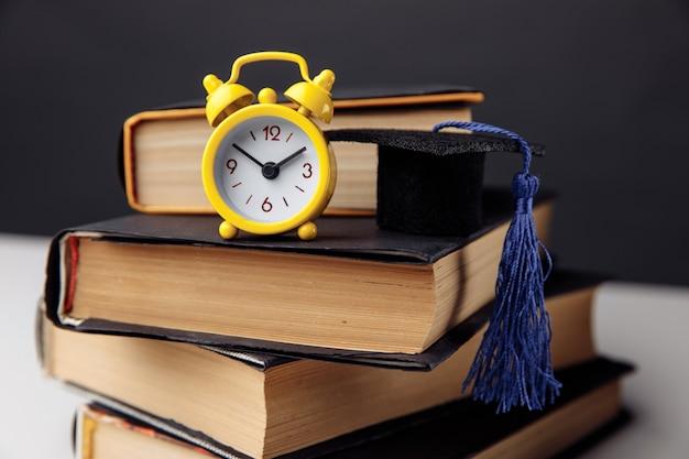Réveil jaune, mini chapeau de graduation et livres sur table.