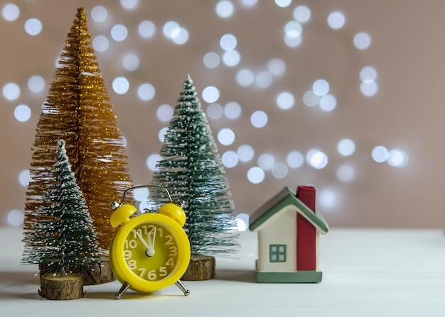 Réveil jaune, petite maison et arbres de noël sur la table
