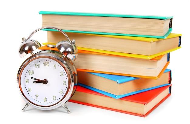 Réveil et livres multicolores sur blanc.