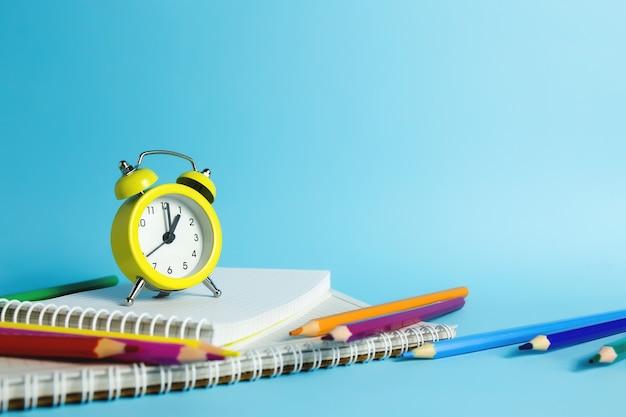 Réveil mécanique, cahier, crayons sur fond bleu. photo de haute qualité