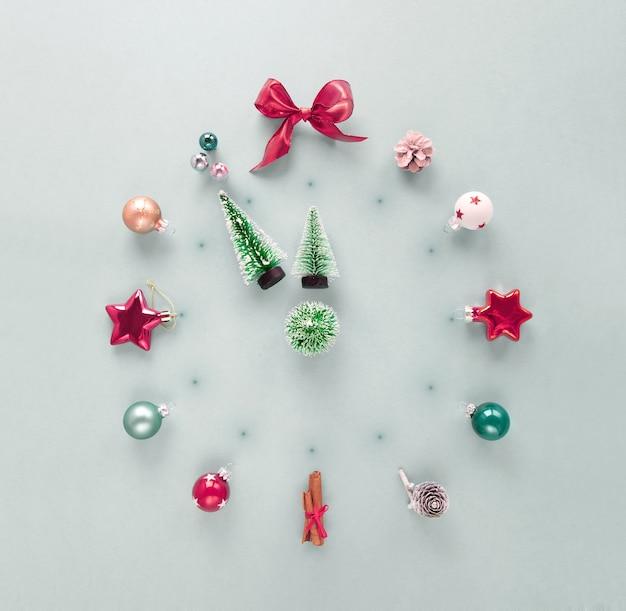 Réveil de noël / cadran de montre présenté avec des décorations de noël: boules, pommes de pin et arbres de noël, flatlay créatif avec espace copie, composition carrée.