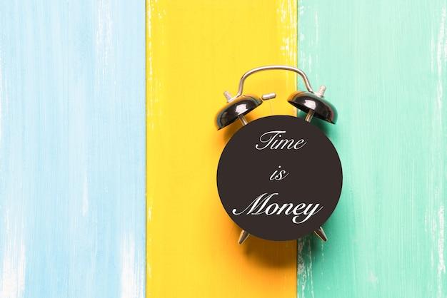 Réveil noir sur des arrière-plans colorés avec le temps de formulation est de l'argent
