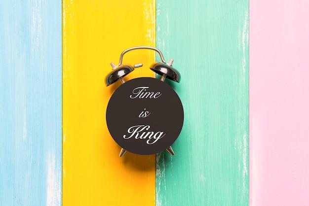 Réveil noir sur des arrière-plans colorés avec le temps de formulation est roi
