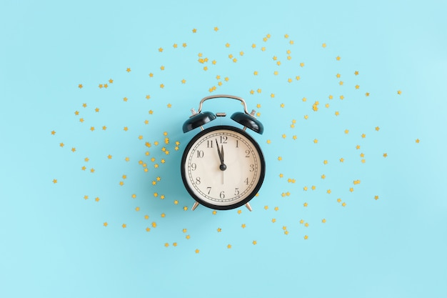 Réveil noir et confettis étoiles d'or sur fond bleu. insomnie, problèmes de sommeil ou doux rêves et bonne nuit. vue de dessus mise à plat espace copie