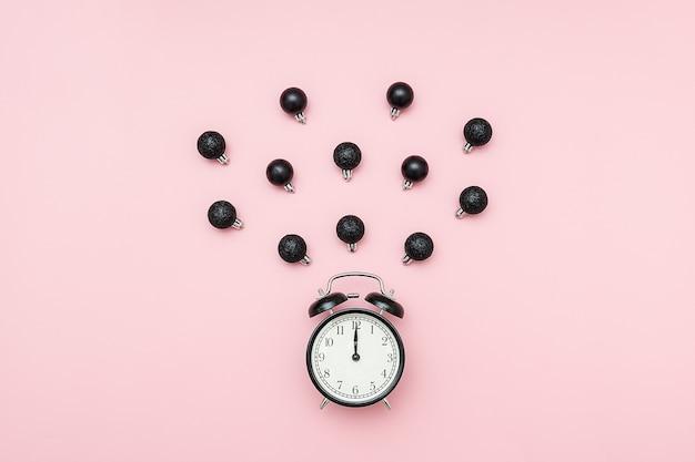 Réveil noir et décorations de noël volantes boules noires sur rose