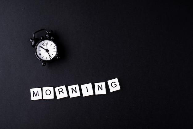 Réveil noir sur fond noir avec les mots matin.