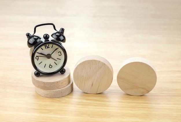 Réveil noir sur la pile de bois rond avec morceau de bois blanc sur la table en bois clair