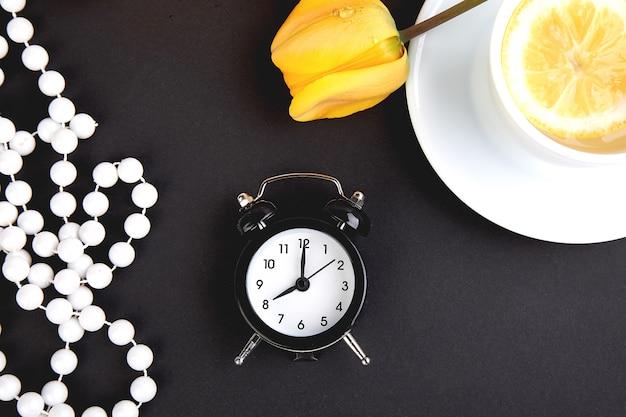 Réveil noir près de bouquet de tulipes jaunes et une tasse de thé au citron. lay plat.