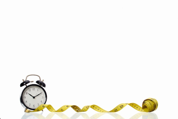 Réveil noir rétro avec ruban à mesurer jaune sur fond blanc concept de réussite
