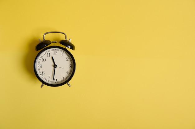 Réveil noir vintage sur fond jaune avec espace de copie pour ajouter du texte. concepts, entreprise, organisation, gestion du temps de la rentrée scolaire et de la journée des enseignants
