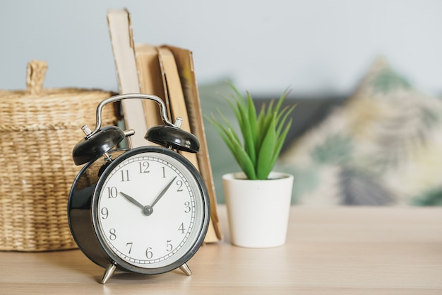 Réveil et objets de bureau se bouchent sur une table en bois