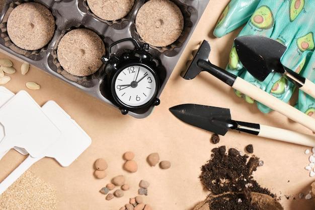 Réveil et outils de jardin sur papier kraft vue de dessus de l'espace de copie, petites plaques de spatules, gants et comprimés de tourbe, tout pour planter des semis