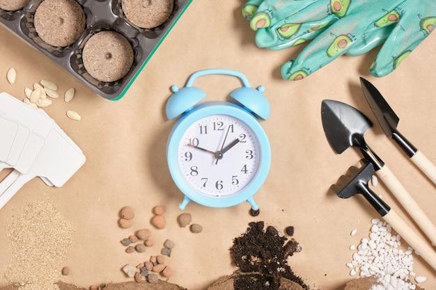 Réveil et outils de jardinage sur papier kraft place copie vue de dessus le temps pour le concept de semis de plantation de printemps