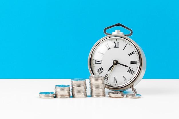 Réveil et pièces d'argent sur la table