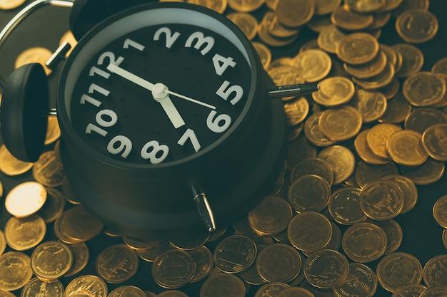 Réveil et pièces de monnaie sur la table de travail