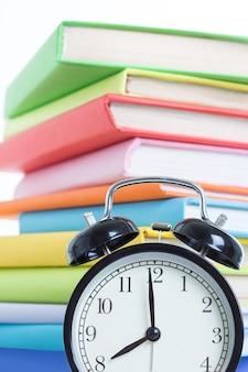 Réveil et pile de livres sur fond blanc