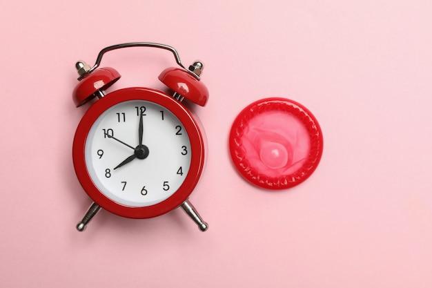 Réveil et préservatif sur mur rose