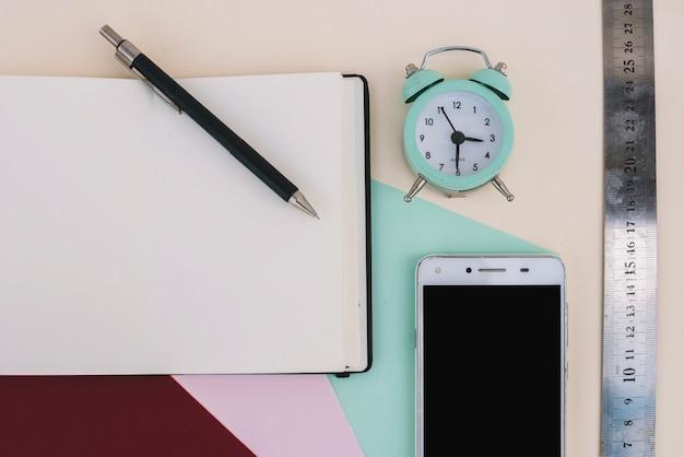 Réveil et règle près de smartphone et ordinateur portable