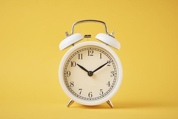 Réveil rétro blanc sur le jaune avec copie espace. concept de temps
