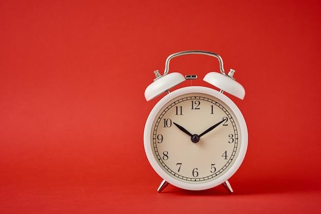 Réveil rétro blanc sur le rouge avec espace de copie. concept de temps