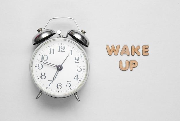 Réveil rétro sur blanc avec texte se réveiller avec des lettres